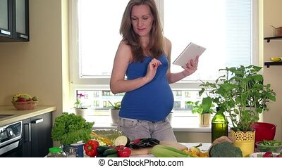 Expectant mother woman using a tablet computer to prepare...