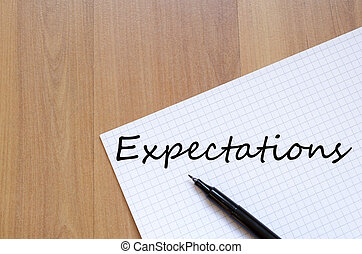 Expectations concept - White blank notepad on office wooden...