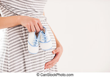 Expecting a boy. Side view cropped image of pregnant woman holding little shoes near abdomen
