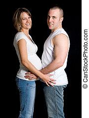 Expecting - expecting couple holding on black background