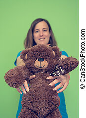 Expecting mother holding a plush bear toy.