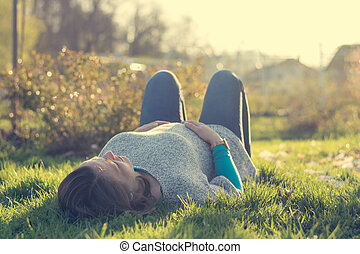 Expecting mother lying on grass in public park.
