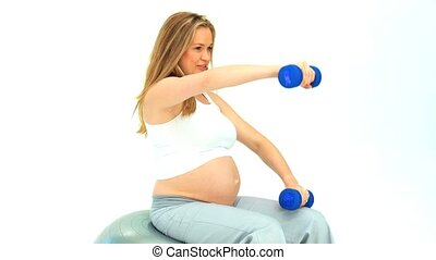 Expecting woman doing exercise with dumbbells on a gym ball