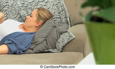 Expecting woman massaging he belly on her sofa