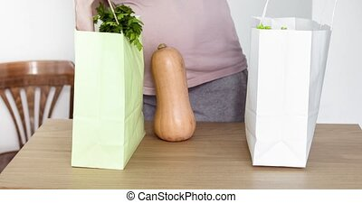 Expecting woman take out vegetables from shopping bag -...