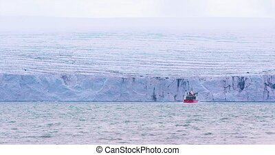 Expedition boat in front of a massive glacier