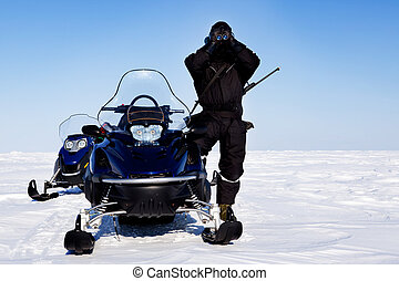 An expedition guide and a couple of snowmobiles on a winter landscape