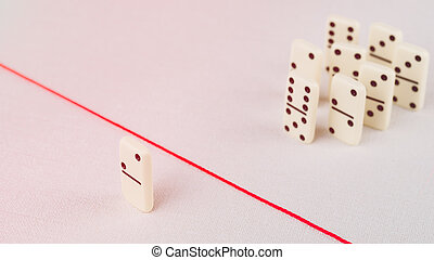 Expelled from the group, unable to cross the red line that separates them. Scene with group of domino. Concept of accusation guilty person, bulling or outcast in the team.