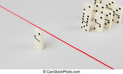 Expelled from the group, unable to cross the red line that separates them. Scene with group of domino. Concept of accusation guilty person, bulling or outcast in the team. Bright background
