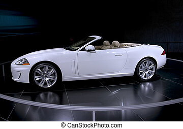 This is an expensive white convertible with a tan interior on display at the auto show with the top down.