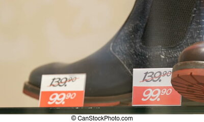Expensive leather luxury boots in shoe showcase store next to the discount price tag close up view