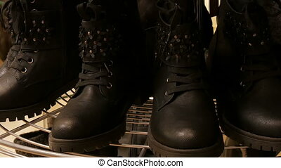 Expensive luxury leather black boots in the shoe showcase store in mall or shopping center