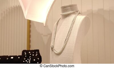 Wonderful expensive pearl necklace on holder near light wall with glowing frame in contemporary jewelry store close view