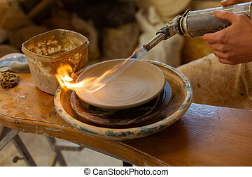 Experience in pottery. Pottery master baking clay plate with special apparat while finishing process of creating