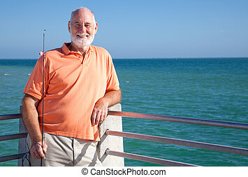 Experienced Angler - Portrait of a happy senior fisherman...