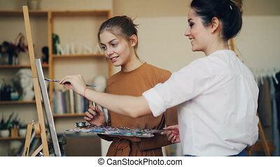 Experienced art teacher is teaching her student to paint...