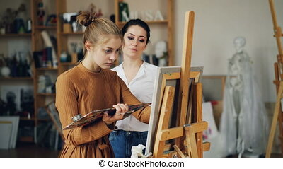 Experienced art teacher is working with pretty girl talanted...