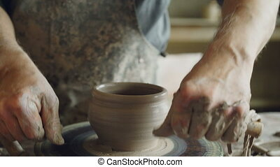 Experienced bearded ceramist is cutting clay pot from...