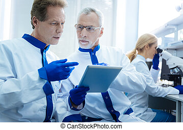 Experienced biologists discussing results displayed on a tablet