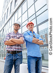 experienced business people in casual clothes and hardhats posing to the camera