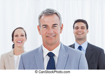 Experienced businessman posing with his work team