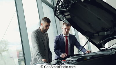 Experienced car dealer is showing new customer engine under...