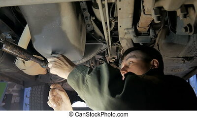 Mechanic repairing car at his workshop