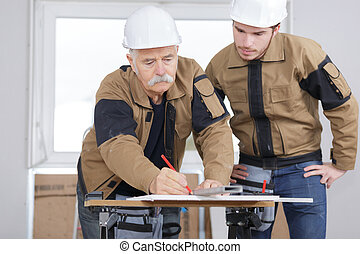experienced carpenter drawing line on piece of wood before cutting
