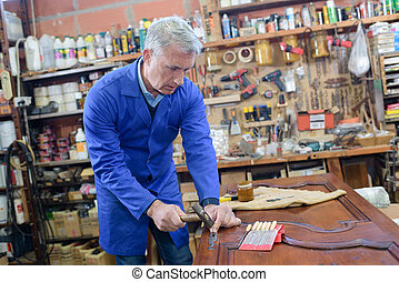 experienced carpenter shaping wood in his old shed