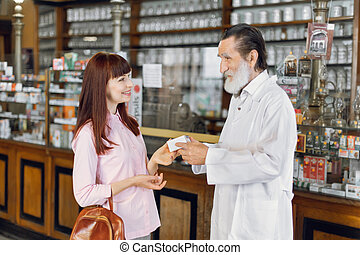 Experienced confident cheerful man pharmacist is recommending safety medicine for young Caucasian woman client in ancient drugstore. Medicine, healthcare concept