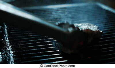 Experienced cook is frying beef slice on grill in kitchen of restaurant.