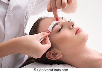 Experienced cosmetician pulling out brows - Calm young girl...