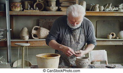 Experienced craftsman is making ear for ceramic bowl and...