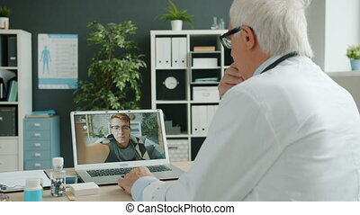 Experienced doctor consulting sick young man patient online ...