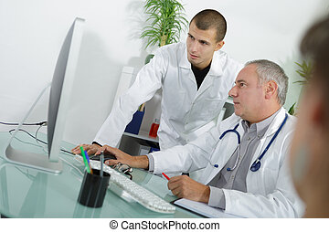 experienced doctor with male assistant in office