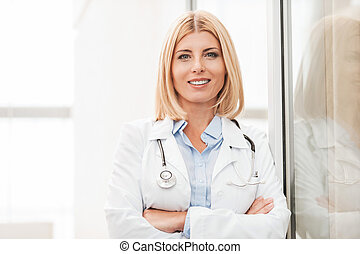 Experienced female doctor. Confident female doctor in white ...