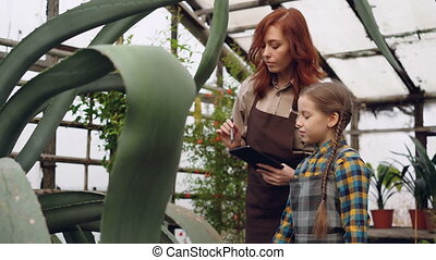 Experienced female gardener and her cute daughter are...