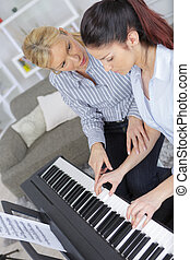 experienced female master piano hand helps the student