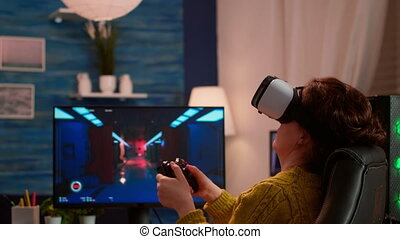 Experienced gamer wearing VR playing at home video game using wireless controller, relaxing at night. Online streaming cyber performing on powerful personal computer during gaming tournament