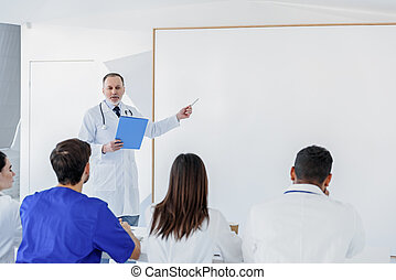 Experienced general practitioner explaining information to students