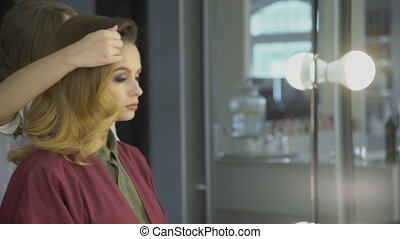 Experienced hairdresser touches hairstyle of sitting lady in salon.