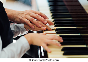 experienced hand of  old music teacher helps  child  pupil