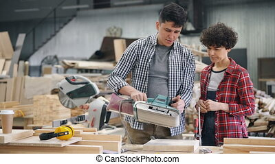 Experienced joiner teaching female apprentice to use belt ...