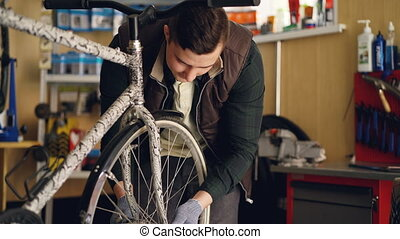 Experienced male master in gloves and vest is fixing bicycle...