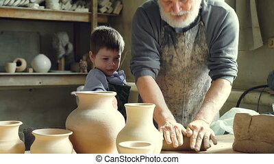 Experienced male potter is mixing and kneading clay while...