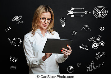 Experienced manager feeling interested while looking at the screen of her tablet