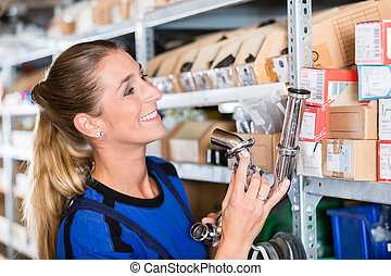 Experienced manual female worker in a sanitary ware shop -...