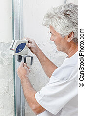 Experienced mason measuring a wall