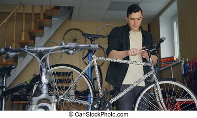 Experienced master is checking and repairing bicycle...