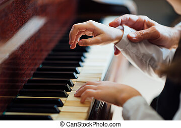 experienced master piano hand helps the student, close-up